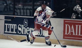 FILE - In this Jan. 7, 1991 file photo, New York Rangers Bernie Nicholls (9) moves the puck while Philadelphia Flyers Craig Berube (17) skates in pursuit during first period action at Madison Square Garden in New York. The Rangers defeated the Flyers 3-2.. The NHL hasn't had best-of-five playoff series since 1986. That's changing for this year with the league expanding to 24 playoff teams as part of its restart. The qualifying round will feature 16 teams facing off in best-of-five series to determine who moves on (AP Photo/Ron Frehm, File)