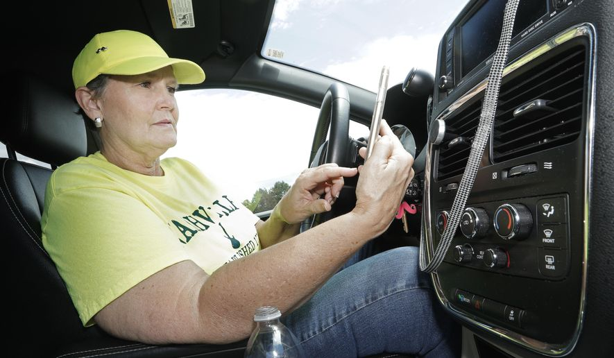 Lyft driver Joni Bicknese checks her phone app between riders Thursday, July 23, 2020, in Nashville, Tenn. Business became dismal after what she calls Nashville's quadruple-whammy: a tornado, coronavirus closures, protests that rocked downtown, then more closures.Bicknese chose to keep driving because she didn't think she could make her car and insurance payments on unemployment. (AP Photo/Mark Humphrey)
