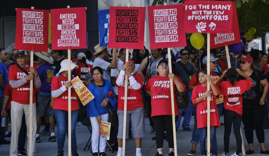 """FILE - Union workers and minimum wage activists gather for a Labor Day rally in downtown Los Angeles, Monday, Sept. 4, 2017. California will raise its minimum wage to $14 an hour next year for workers at larger companies, hitting businesses with higher costs even at a time when many are struggling amid the coronavirus pandemic. """"Not allowing this increase to go forward will only make life harder for those Californians who have already borne a disproportionate share of the economic hardship caused by this pandemic,"""" Gov. Gavin Newsom says. (AP Photo/Richard Vogel, File)"""