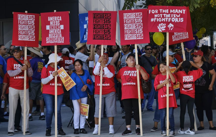 "FILE - Union workers and minimum wage activists gather for a Labor Day rally in downtown Los Angeles, Monday, Sept. 4, 2017. California will raise its minimum wage to $14 an hour next year for workers at larger companies, hitting businesses with higher costs even at a time when many are struggling amid the coronavirus pandemic. ""Not allowing this increase to go forward will only make life harder for those Californians who have already borne a disproportionate share of the economic hardship caused by this pandemic,"" Gov. Gavin Newsom says. (AP Photo/Richard Vogel, File)"