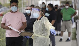FILE - In this July 22, 2020, file photo, people line up behind a health care worker at a mobile Coronavirus testing site at the Charles Drew University of Medicine and Science, in Los Angeles. Los Angeles County is seeing some hopeful signs amid the coronavirus surge. The county reported Wednesday that COVID-19 hospitalization and transmission rates are dropping. (AP Photo/Marcio Jose Sanchez, File)