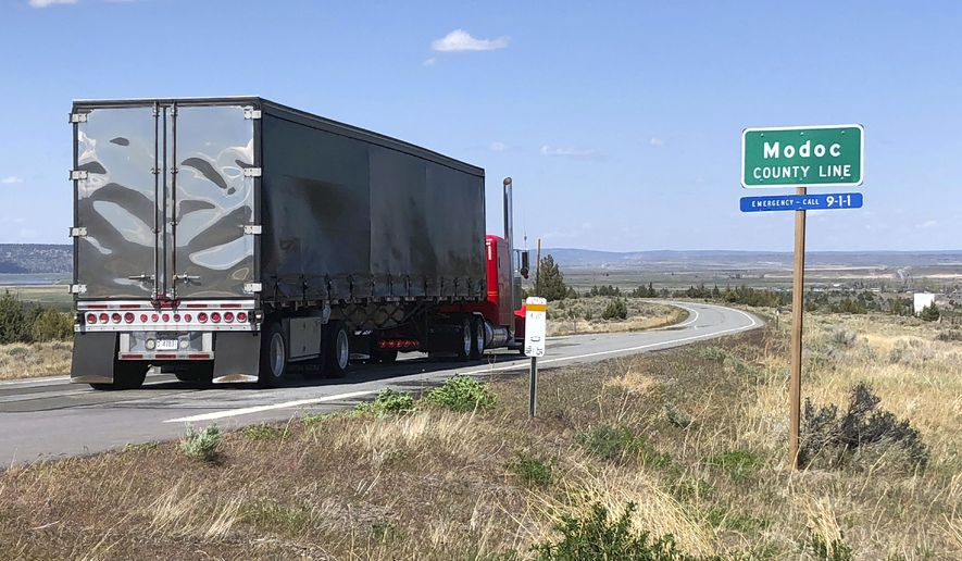 FILE - In this Friday, May 1, 2020 file photo, a northbound truck crosses the Modoc County line in Northern California along the high Sierra's eastern front, about 160 miles north of Reno, Nev., near Likely, Calif. The rural California county that was the first to defy state shutdown orders intended to prevent spread of the coronavirus has recorded its first cases of COVID-19. Lightly populated Modoc County in the far northeast corner of the state has two confirmed cases of COVID-19 from the same household, according to a county Public Health Department press release Tuesday, July 28, 2020.The department said it was identifying people who may have had close contact with the individuals, who have not been hospitalized. The department also asked anyone who patronized a local bar to call in. (AP Photo/Scott Sonner, File)