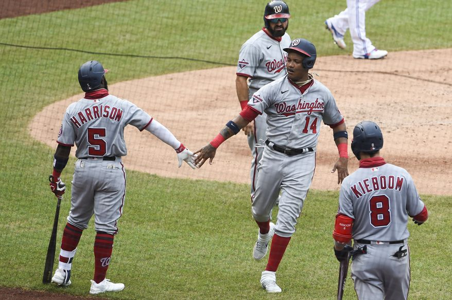 Washington Nationals second baseman Starlin Castro (No. 14) celebrates with Josh Harrison and other teammates after scoring a run against the Toronto Blue Jays on Thursday, July 30, 2020, at Nationals Park in Washington, D.C. (Photo by All-Pro Reels)