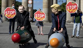 Two activists dressed up as U.S. President Trump and Russian President Putin ride two atomic bomb models during a protest for a world without nuclear weapons in front of the Brandenburg Gate in Berlin, Germany, July 30, 2020. Several peace and disarmament organizations as well as environmental protection groups demonstrated on the Pariser Platz for a nuclear weapons-free world before the start of negotiations between the USA and Russia on further action in nuclear arms control. (Fabian Sommer/dpa via AP)