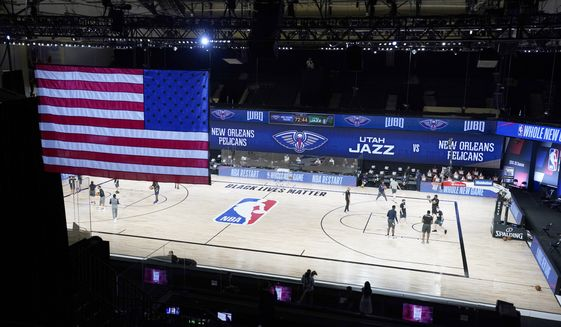 Members of the New Orleans Pelicans and Utah Jazz warm up before the start of an NBA basketball game with no fans in the stands as seen in this general view Thursday, July 30, 2020, in Lake Buena Vista, Fla. (AP Photo/Ashley Landis, Pool)