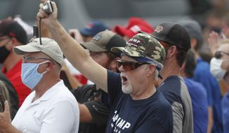 """Supporters cheer and take pictures as Vice President Mike Pence speaks at a """"Cops for Trump"""" campaign event at the police station, Thursday, July 30, 2020, in Greensburg, Pa. (AP Photo/Keith Srakocic)"""