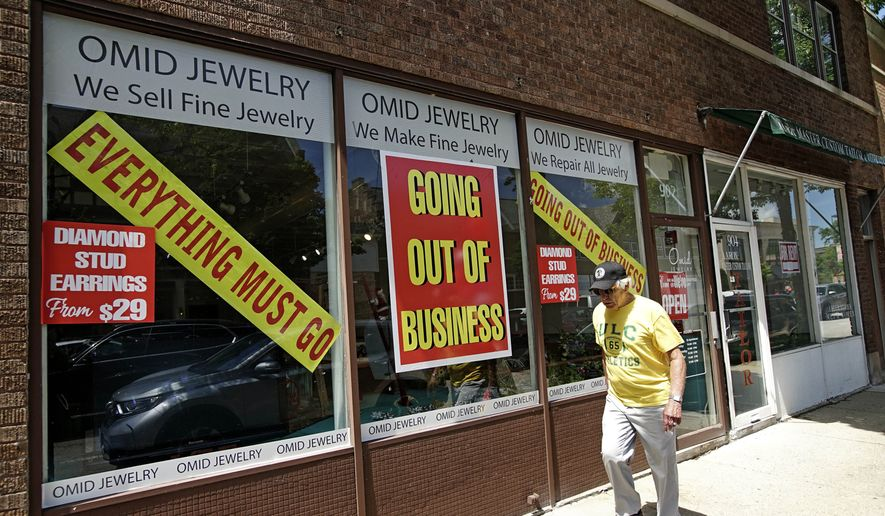 A man walks past a retail store that is going out of business due to the coronavirus pandemic in Winnetka, Ill., Tuesday, June 23, 2020. More than 1.4 million laid-off Americans applied for unemployment benefits last week, reported Thursday, July 30, further evidence of the devastation the coronavirus outbreak has unleashed on the U.S. economy. (AP Photo/Nam Y. Huh)