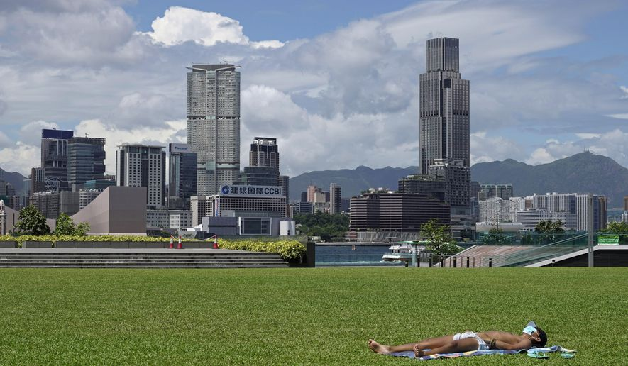 A man sunbathes at a park in Hong Kong Thursday, July 30, 2020. As of Wednesday, Hong Kong reported over 3,000 coronavirus infections, with dozens of deaths. Businesses such as bars, karaoke bars and amusement parks remain temporarily closed. (AP Photo/Vincent Yu)