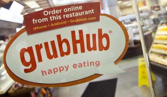 FILE - In this April 4, 2014 file photo, a sign with the old GrubHub logo is displayed is displayed on the door to a New York restaurant.  Grubhub saw its average daily orders jump 32% in the second quarter, Thursday, July 30, 2020,  but swung to a loss as it spent heavily to prop up restaurants and protect drivers.(AP Photo/Mark Lennihan, File)