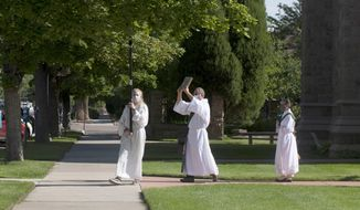 This photo provided by Kaiser Health News shows, from left, Abigail Sena leads the procession as an acolyte, followed by Gary Darress, a deacon, and Claire Elser, a curate, during worship services on Sunday, July 19, 2020, at Grace and St. Stephen's Episcopal Church in Colorado Springs, Colo. The church offers socially distant, outdoor Sunday worship services, in which attendees can sit spaced out on the lawn or listen on the radio from their cars. The evangelical stronghold of Colorado Springs has returned to the church in ways both guarded and full of gusto during the coronavirus pandemic. The state still limits how many people can gather and recommends social distancing practices. (Rachel Woolf for KHN via AP)