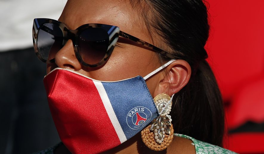 Supporter wearing PSG face mask looks on during a friendly soccer match between Paris Saint Germain and Glasgow Celtic FC at Parc des Princes Stadium in Paris, Tuesday, July 21, 2020. (AP Photo/Francois Mori)
