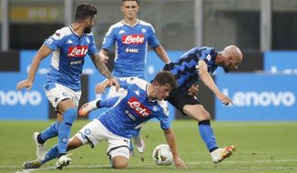Napoli's Diego Demme, centre, tries to stop Inter Milan's Borja Valero, right, during the Serie A soccer match between Inter Milan and Napoli at the San Siro Stadium, in Milan, Italy, Tuesday, July 28, 2020. (AP Photo/Antonio Calanni)