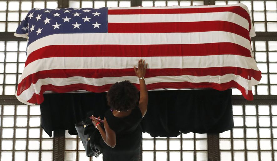 A mourner pauses by the casket of Rep. John Lewis lying in repose at the state capital, Wednesday, July 29, 2020, in Atlanta. Lewis, who carried the struggle against racial discrimination from Southern battlegrounds of the 1960s to the halls of Congress, died Friday, July 17, 2020. (AP Photo/John Bazemore)