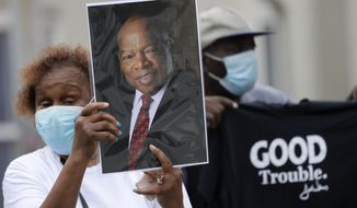 Mourners stand outside Ebenezer Baptist Church during the funeral for Rep. John Lewis at , Thursday, July 30, 2020, in Atlanta. Lewis, who carried the struggle against racial discrimination from Southern battlegrounds of the 1960s to the halls of Congress, died Friday, July 17, 2020. (AP Photo/Brynn Anderson)