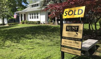 FILE - In this May 22, 2020 file photo a sold sign stands in front of a house in Brighton, N.Y. U.S. average rates on long-term mortgages declined this week, remaining near historic lows as the key 30-year loan slipped back below 3%. Mortgage buyer Freddie Mac reports the average rate on the 30-year home loan eased to 2.99% from 3.01% last week. (AP Photo/Ted Shaffrey, File)