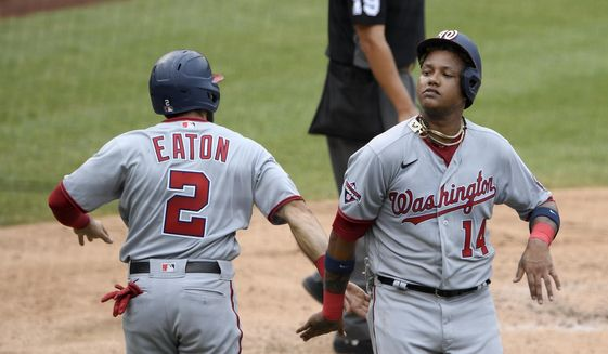 Washington Nationals' Starlin Castro (14) celebrates with Adam Eaton (2) after both scored on a double by Kurt Suzuki during the third inning of the team's baseball game against the Toronto Blue Jays, Thursday, July 30, 2020, in Washington. (AP Photo/Nick Wass)