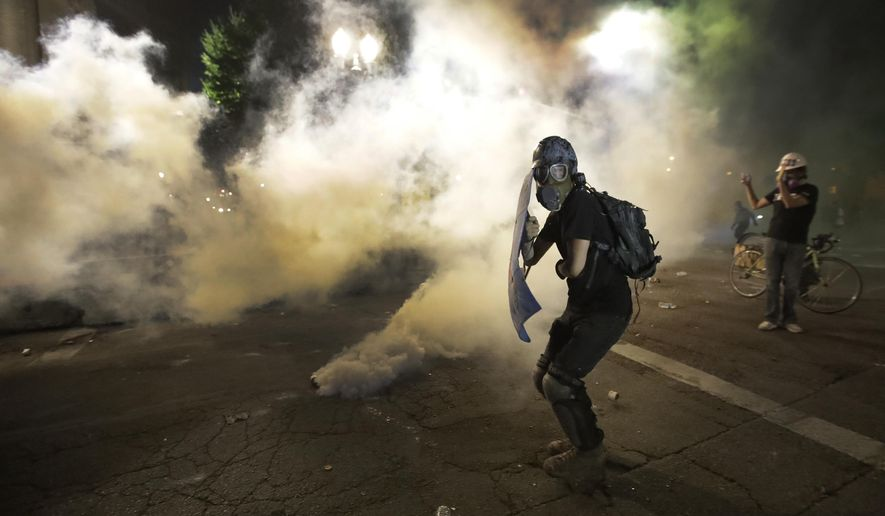 A demonstrator tries to shield himself from tear gas deployed by federal agents during a Black Lives Matter protest at the Mark O. Hatfield United States Courthouse Wednesday, July 29, 2020, in Portland, Ore. (AP Photo/Marcio Jose Sanchez)