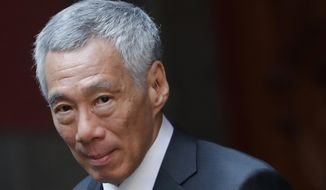 FILE - In this Nov. 19, 2019, file photo, Singaporean Prime Minister Lee Hsien Loong walks at the National Palace in Mexico City. A Singapore court has fined the nephew of Lee Singapore dollars 15,000 ($10,900) for criticizing the judiciary in a Facebook posting two years ago amid a public feud in the first family. (AP Photo/Marco Ugarte, File)