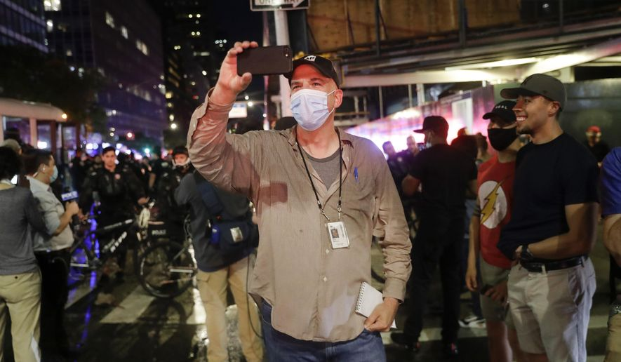 Associated Press NBA reporter Brian Mahoney records video while covering a protest, Wednesday, June 3, 2020, in New York. When the NBA season was suspended and he was reassigned to the news department,heI assumed it was just to report from here. But, according to Mahoney, there were so many coronavirus stories to tell: Health care workers trying to keep patients alive. Residents of a community who all knew somebody who had died.   (AP Photo/Seth Wenig)
