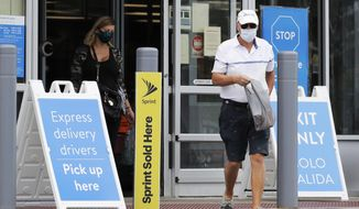 Shoppers wear face masks as they leave a Walmart store in Vernon Hills, Ill., Thursday, July 30, 2020. Many retail stores are requiring customers to wear face masks inside all of their stores where local governments do not require it amid the coronavirus pandemic. However, limited enforcement, at Walmart avoids physical confrontations with customers who refuse to wear mask. (AP Photo/Nam Y. Huh)