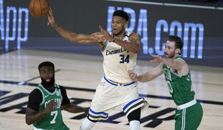 Milwaukee Bucks' Giannis Antetokounmpo (34) passes around Boston Celtics' Jaylen Brown (7) and Gordon Hayward during the first half of an NBA basketball game Friday, July 31, 2020, in Lake Buena Vista, Fla. (AP Photo/Ashley Landis, Pool)