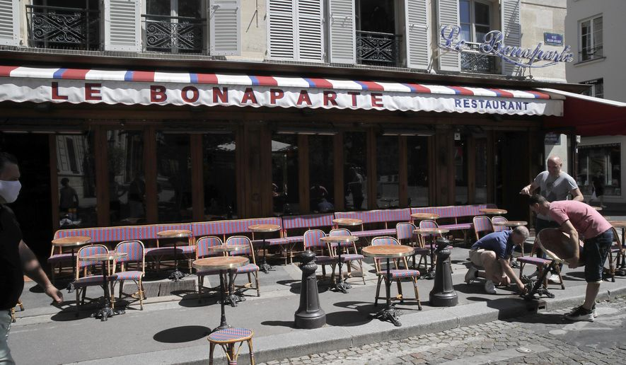 In this June 1, 2020, file photo, waiters prepare the terrace of a restaurant in order to respect distancing measures in Paris as France gradually lifts its lockdown due to the coronavirus. France's economy shrank by nearly 14% in the second quarter when the country was in coronavirus lockdown, a third consecutive quarter of negative growth in a worsening recession, the national statistics agency said Friday, July 31, 2020. (AP Photo/Christophe Ena, File)