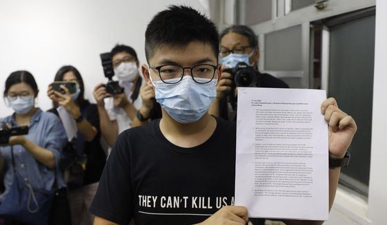 Hong Kong pro-democracy activist Joshua Wong shows his disqualification notice during a press conference in Hong Kong, Friday, July 31, 2020. On Thursday, 12 pro-democracy candidates including prominent pro-democracy activist Joshua Wong were disqualified from running in the legislative elections, as they were deemed to not comply with the Basic Law or pledge allegiance to the city and Beijing. (AP Photo/Kin Cheung)