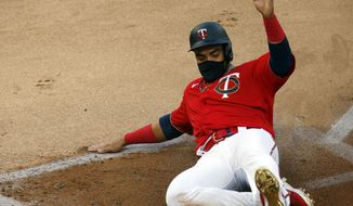 Minnesota Twins' Nelson Cruz scores on a two-run double by Eddie Rosario off Cleveland Indians' pitcher Mike Clevinger in the first inning of a baseball game Friday, July 31, 2020, in Minneapolis. (AP Photo/Jim Mone)