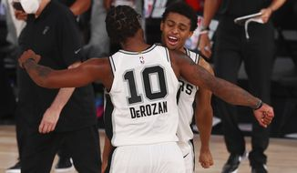 San Antonio Spurs forward DeMar DeRozan (10) celebrates with forward Keldon Johnson (3) after defeating the Sacramento Kings in an NBA basketball game Friday, July 31, 2020, in Lake Buena Vista, Fla. (Kim Klement/Pool Photo via AP)