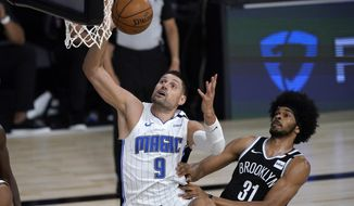 Orlando Magic's Nikola Vucevic (9) heads to the basket as Brooklyn Nets' Jarrett Allen (31) defends during the first half of an NBA basketball game Friday, July 31, 2020, in Lake Buena Vista, Fla. (AP Photo/Ashley Landis, Pool)