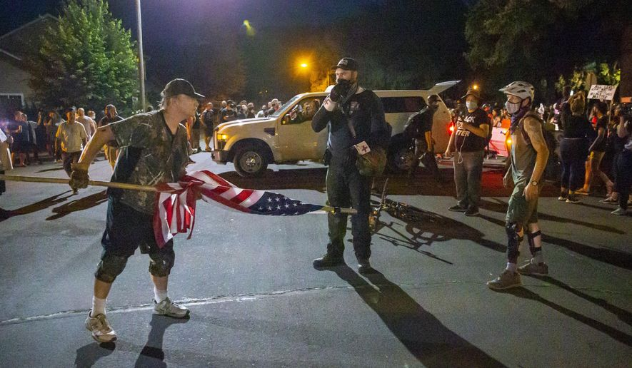 A Thurston neighborhood resident and a Black Unity protester square off as Black Unity protesters left the Springfield, Ore., neighborhood after marching through the streets in Springfield, Ore. July 29, 2020. (Andy Nelson/The Register-Guard via AP)