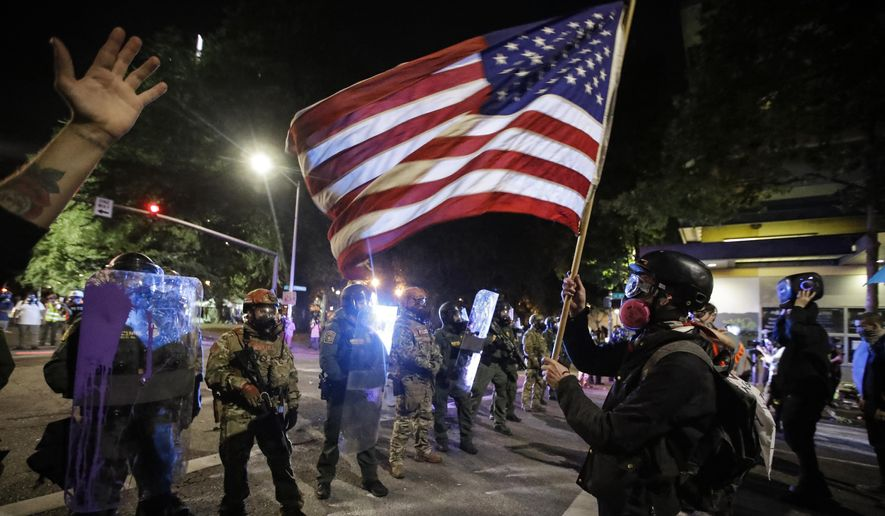 A demonstrator waves a U.S. flag in front of federal officers after tear gas is deployed during a Black Lives Matter protest at the Mark O. Hatfield United States Courthouse Thursday, July 30, 2020, in Portland, Ore. (AP Photo/Marcio Jose Sanchez)