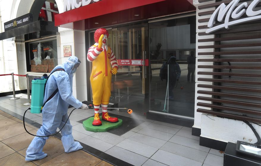 An employee disinfects a closed mall in Mumbai, Thursday, July 30, 2020. Malls and market complexes will reopen on Aug. 5. However theaters, food courts and gyms will remain closed. (AP Photo/Rafiq Maqbool)