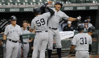 New York Yankees' Luke Voit (59) celebrates with Giancarlo Stanton, center right, after hitting a grand slam off Baltimore Orioles starting pitcher John Means during the first inning of a baseball game, Thursday, July 30, 2020, in Baltimore. Yankees' Gleyber Torres, Aaron Hicks (31) and Stanton scored on the grand slam. (AP Photo/Julio Cortez)