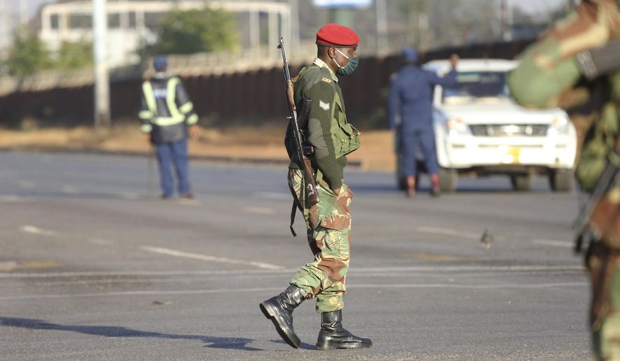 Armed soldiers patrol a street in Harare, Friday, July, 31, 2020. Zimbabwe's capital, Harare, was deserted Friday, as security agents vigorously enforced the country's lockdown amidst planned protests.Police and soldiers manned checkpoints and ordered people seeking to get into the city for work and other chores to return home. (AP Photo/Tsvangirayi Mukwazhi)