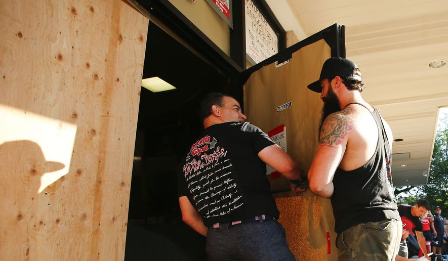 Owners of Atilis Gym in Bellmawr, N.J., Ian Smith, right, and Frank Trumbetti replace the front door on its hinges before reopening for members Saturday, Aug. 1, 2020. The owners of the gym that has repeatedly defied Gov. Phil Murphy's executive order to remain closed during the COVID-19 pandemic have once again reopened the facility less than a week after their arrests on contempt charges. (Yong Kim/The Philadelphia Inquirer via AP)