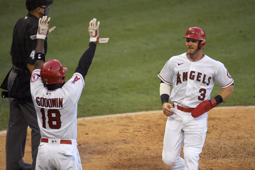 Los Angeles Angels' Taylor Ward, right, scores on a sacrifice fly hit by David Fletcher as Brian Goodwin (18) celebrates during the sixth inning of a baseball game against the Houston Astros, Saturday, Aug. 1, 2020, in Anaheim, Calif. (AP Photo/Mark J. Terrill)