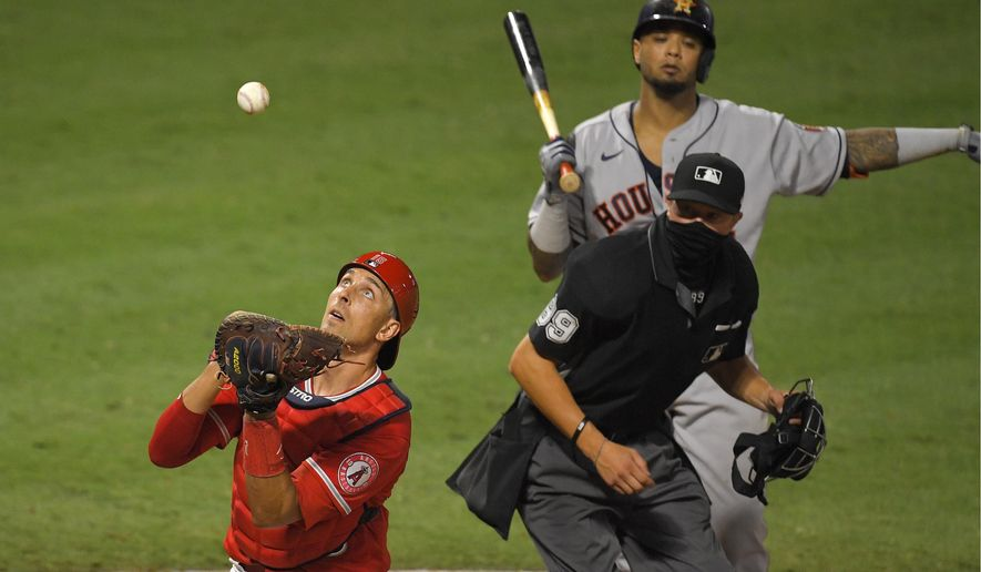 Los Angeles Angels catcher Jason Castro, left, catches a ball that was fouled off the ground by Houston Astros' Martin Maldonado, upper right, as home plate umpire Cory Blaser watches during the ninth inning of a baseball game Friday, July 31, 2020, in Anaheim, Calif. Houston Astros' Myles Straw advanced to second on the play. (AP Photo/Mark J. Terrill)