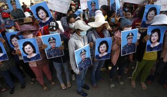 Cambodian garment workers holding the portraits of Prime Minister Hun Sen and his wife Bun Rany stage a protest rally near the prime minister's residence in Phnom Penh, Cambodia, Wednesday, July 29, 2020. Some 200 workers on Wednesday submitted a petition to Hun Sen in the hopes to solve their problem with their factory owner who they say has refused to pay benefits after the factory closed earlier in July.  (AP Photo/Heng Sinith)