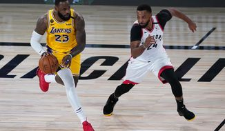 Los Angeles Lakers' LeBron James (23) drives into Toronto Raptors' Norman Powell (24) during the first half of an NBA basketball game Saturday, Aug. 1, 2020, in Lake Buena Vista, Fla. (AP Photo/Ashley Landis, Pool)