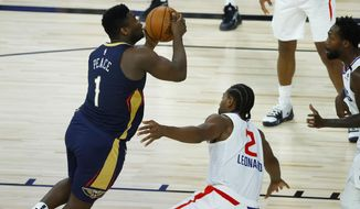 New Orleans Pelicans' Zion Williamson, left, drives to the basket against Los Angeles Clippers' Kawhi Leonard during an NBA basketball game Saturday, Aug. 1, 2020, in Lake Buena Vista, Fla. (Kevin C. Cox/Pool Photo via AP)