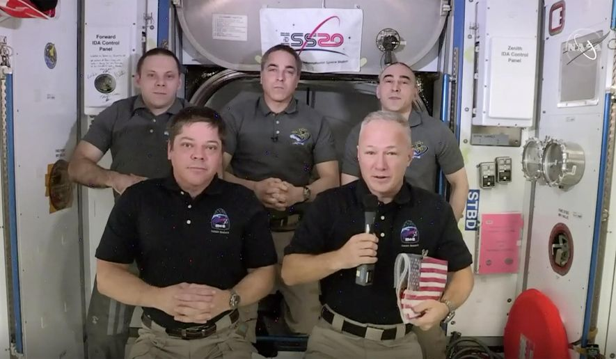 This photo provided by NASA shows, from left, front, astronauts Bob Behnken and Doug Hurley during an interview on the International Space Station on Saturday, Aug. 1, 2020. Behnken and Hurley are scheduled to leave the International Space Station in a SpaceX capsule on Saturday and splashdown off the coast of Florida on Sunday. (NASA via AP)