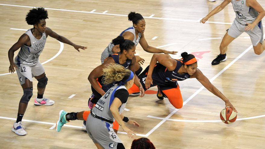 Connecticut Sun's Brionna Jones, right, reaches for a loose ball as Minnesota Lynx's Shenise Johnson (42) and Rachel Banham (15) watch during the first half of a WNBA basketball game Saturday, Aug. 1, 2020, in Bradenton, Fla. (AP Photo/Steve Nesius)