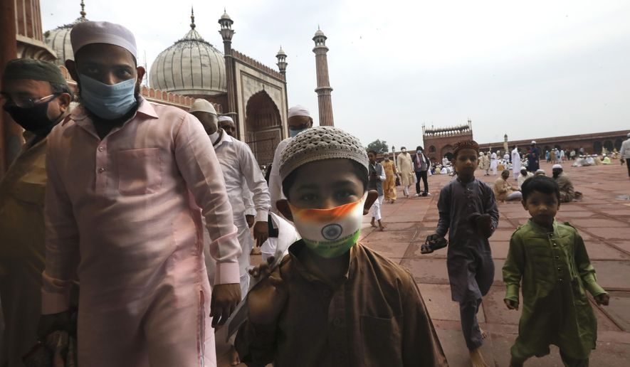 An Indian Muslim boy wears a protective mask in the colors of the Indian national flag, leaves  after offering Eid al-Adha prayer at the Jama Masjid in New Delhi, India, Saturday, Aug.1, 2020. Eid al-Adha, or the Feast of the Sacrifice, by sacrificing animals to commemorate the prophet Ibrahim's faith in being willing to sacrifice his son. (AP Photo/Manish Swarup)