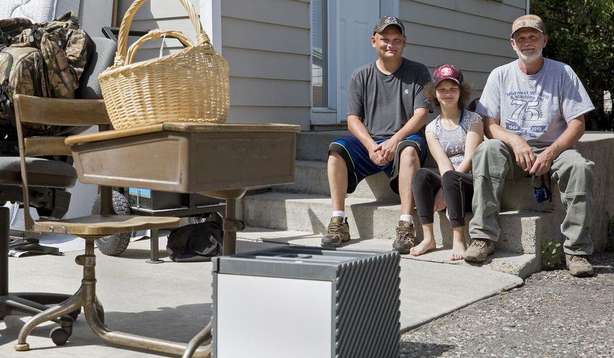From left, Mike Banderob, 38, Rose Banderob, 11, and Scott Banderob, 58, host a garage sale in order to raise money to pay for rent and other expenses on Friday, July 31, 2020, in Bozeman, Mont. Their landlord is planning to evict them in September, refusing to accept money from the CARES Act Housing Assistance Program or other local non-profits attempting to intercede on the Bandrob's behalf.  . (Rachel Leathe/Bozeman Daily Chronicle via AP)