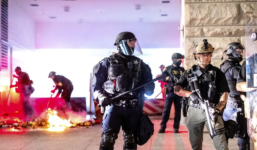 An Oregon State Police officer, right, stands watch as fellow officers extinguish a fire lit by protesters behind the Mark O. Hatfield United States Courthouse on Sun, Aug. 2, 2020, in Portland, Ore. Following an agreement between Democratic Gov. Kate Brown and the Trump administration to reduce federal officers in the city, nightly protests remained largely peaceful without major confrontations between protesters and officers. (AP Photo/Noah Berger)