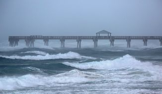 Waves are driven by Tropical Storm Isaias at the Juno Beach Pier Sunday, Aug. 2, 2020. (Lannis Waters/The Palm Beach Post via AP)
