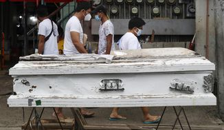 "People pass by an empty coffin placed outside a public market to remind people to stay home as the government relaxes quarantine measures against the COVID19 on Sunday, Aug. 2, 2020 in Manila, Philippines. Coronavirus infections in the Philippines continues to surge Sunday as medical groups declared the country was waging ""a losing battle"" against the contagion and asked the president to reimpose a lockdown in the capital. (AP Photo/Aaron Favila)"