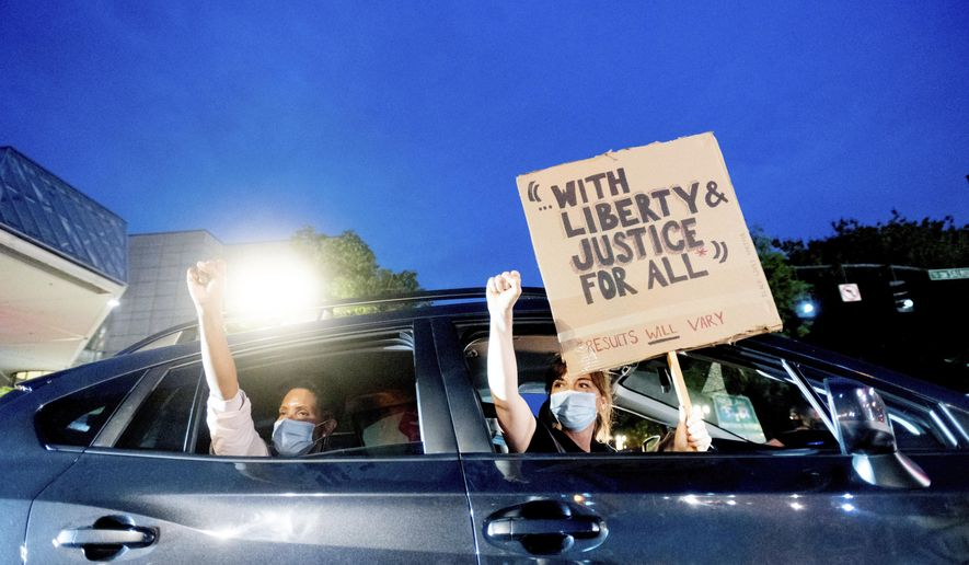 Bobbi Snethen, right, holds a sign during a protest caravan for Black Lives Matter on Friday, July 31, 2020, in Portland, Ore. Following an agreement between Democratic Gov. Kate Brown and the Trump administration to reduce federal officers in the city, nightly protests remained largely peaceful without major confrontations between demonstrators and officers. (AP Photo/Noah Berger)