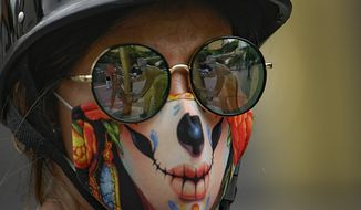 "The ""Oilworkers"" sculpture by Beatriz Blanco is reflected in the sunglasses of a woman wearing a stylized protective face mask as a precaution against the new coronavirus, on Sabana Grande boulevard in Caracas, Venezuela, Saturday, Aug. 1, 2020. (AP Photo/Matias Delacroix)"